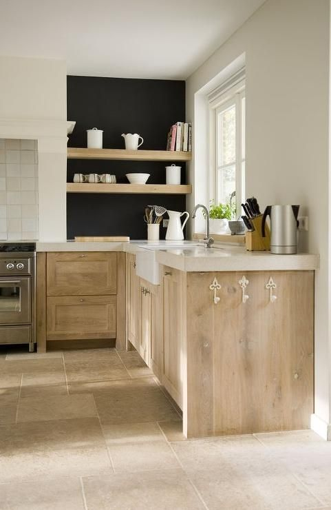 Lovely European kitchen features lightly stained cabinets fitted with white fleur de lis hooks paired with thick cream countertops framing a farmhouse sink and gooseneck faucet under window sill topped with plants as well  as mortar and pestle.