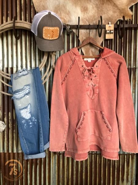 The Missoula - Distressed lace-up hoodie. Acid washed cinnamon/coral color. Embroidered accents on front pocket and shoulders. V-cut neckline with lace up detail. Split hem sides.