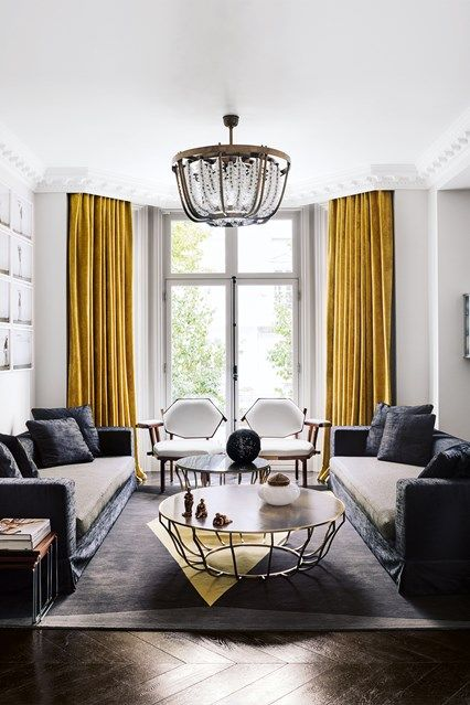 Bright mustard-yellow curtains anchor this grey and white modern living room in a Victorian house designed by Shalini Misra. White walls and herringbone wooden floors provide a clean canvas against which the intricate lines of the pendant lamp and coffee
