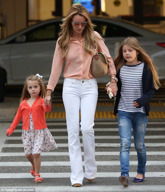 What a stunner: Holding hands with her beloved children, the pretty blonde tucked in a cor...