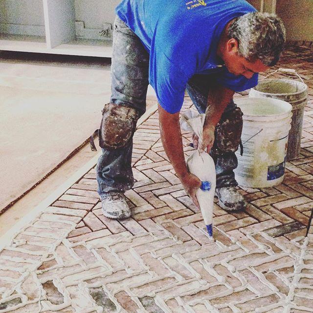 A craftsman employing the tricks of the trade -- a pastry bag full of mortar -- to install a herringbone-pattern brick floor #weidnerhasou #herringbonefloor #brickfloor #skilledcraftsman @scoutguidehouston #houstondesign Design by Weidner + Hasou Design
