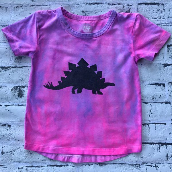 Made for those of you who aren't afraid of colour, these tees are unisex and on premium stock.  They come in three amazing colour schemes, Sunrise, Hyper Bomb and Ocean. Each one is hand dyed by me, making it individual and unique just like your roarsome kid!  Pink and Purple hand dyed shirt with screen printed stegosaurus dinosaur shirt for kids.  Tie Dyed