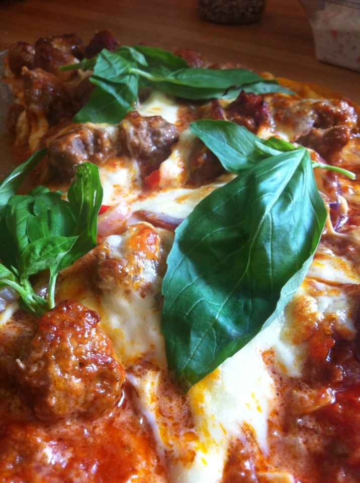Homemade spicy meat feast pizza topped with fresh basil. A real winter warmer.