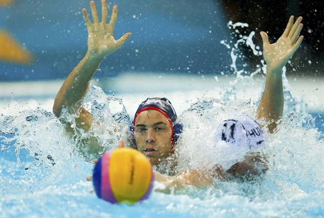 Timothy Hutten competes for possession with Hungary's Adam Steinmetz during their preliminary round Group B water polo match at the Water Polo Arena.