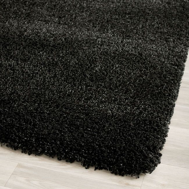 This fuzzy shag rug is a modern accent for any setting. It offers a cozy appearance that is contemporary and vivid. This power-loomed black shag rug is made from polypropylene and can complement similar color schemes in rooms and living spaces.