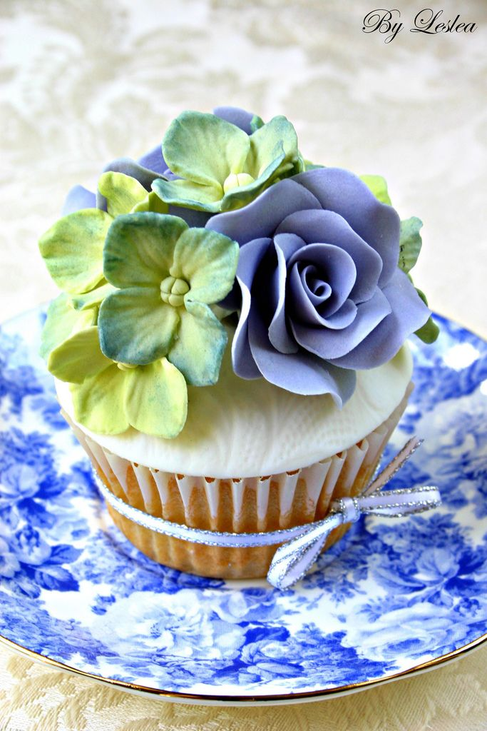 Double vanilla cupcake with hydrangea blue and green roses.