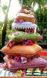 Pillow wedding cake.  Blue, green, orange, purple and yellow with flowers.