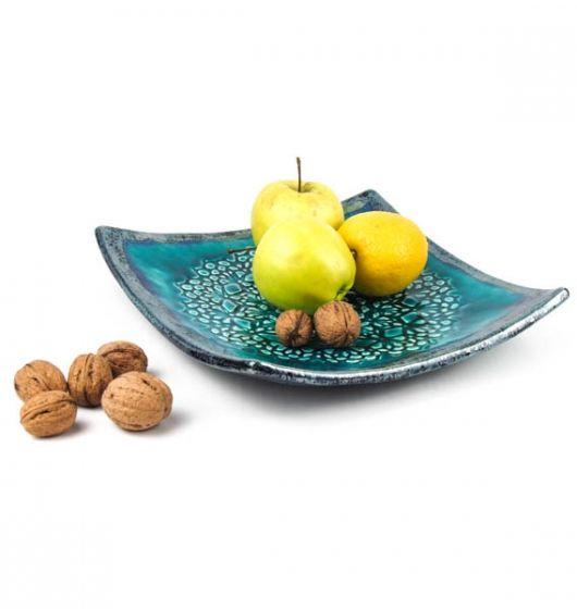 Kwadratowy talerz (patera) z motywem koronki. Ceramika formowana ręcznie, dwukrotnie wypalana. Środek turkusowy (z efektem spękań crackle) a brzegi i spód granatowo-srebrno-zielone. Wymiary: 25 x 25 cm.