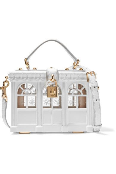 Dolce & Gabbana's elaborately constructed clutch is inspired by the classic styles worn by '50s screen icons. It's masterfully carved from wood to resemble a garden house and hand-painted in fresh white. This structured piece is finished with a gilded padlock and the brand's signature enameled flower. Detach the lizard-effect leather strap to carry yours in-hand.