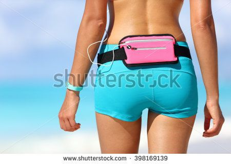 Running sports gear wearable tech female runner wearing fitness smart watch and smartphone holder waist pack for listening to music during outdoor workout. Closeup of shorts and behind.