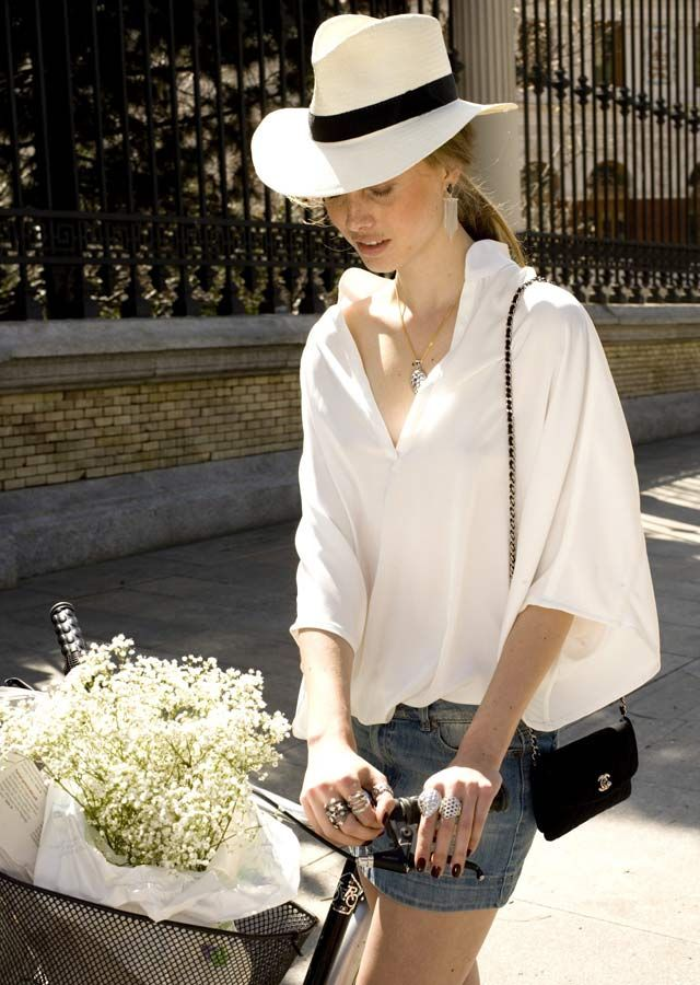 loose flowy oversized white silk blouse paired with jhorts (aka: jean shorts/cutoffs)vand a straw fedora