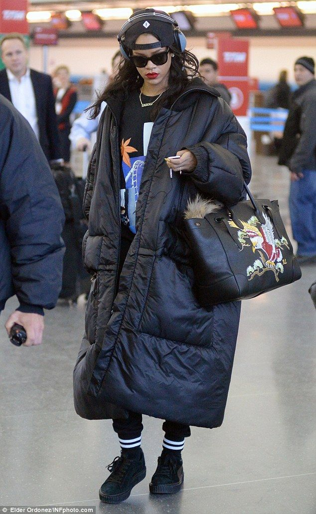 Serious: Rihanna failed to raise a smile and looked deep in thought as she checked her phone as she arrived at JFK airport on Wednesday