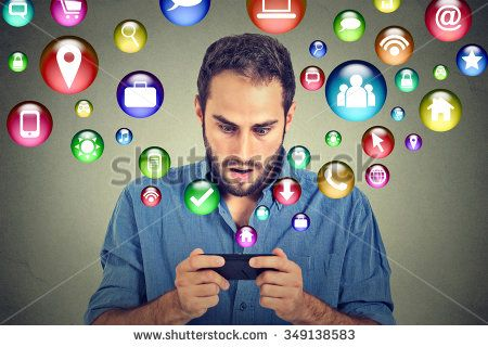 communication technology mobile phone high tech concept. Shocked handsome man using texting on smartphone application icons flying out of cellphone screen isolated on grey background. Face expression