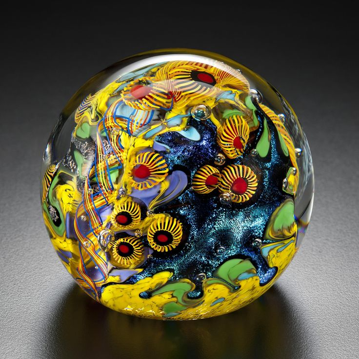 Canary Islands Paperweight by David Lindsay. The artist hand sculpts murrini, frit, and dichroic glass within a clear glass surround, creating an otherworldly paperweight full of radiant color and dynamic texture. Each piece is unique and will vary.