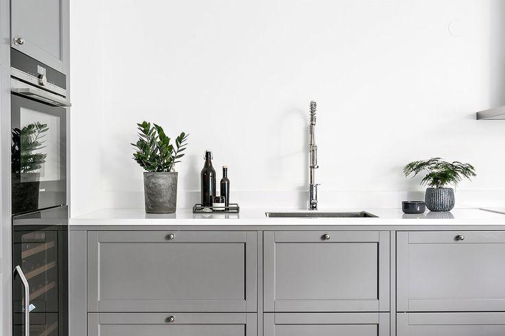 Kök från Ballingslöv med gott om förvaring bakom gråa speglade skåpluckor och rejäla arbetsytor på vit bänkskiva i kompositsten som vinklas upp mot vägg som stänkskydd. Utöver det är köket mycket genomtänkt med vägguttag, blandare och placering för maximal komfort och funktion.