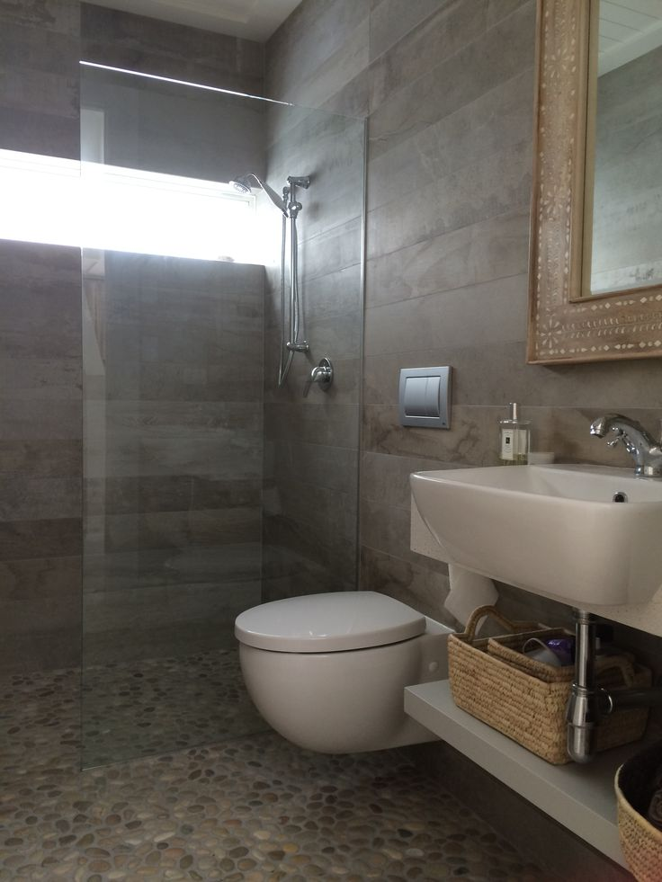 Downstairs bathroom using Island Stone's pebble floor French Tan.  Love my mirror from Indie Home Collective.