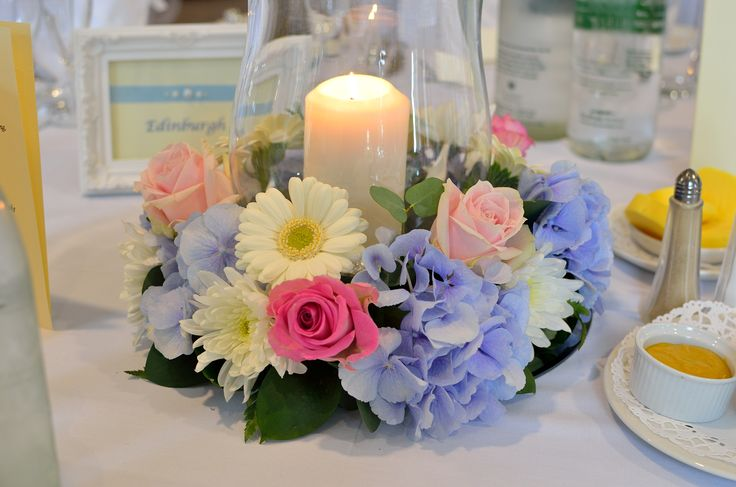 Traditional hurricane candle lamp with roses, hydrangeas, gerberas, chrysanthemums and wax flower-a timeless English wedding table centrepiece.