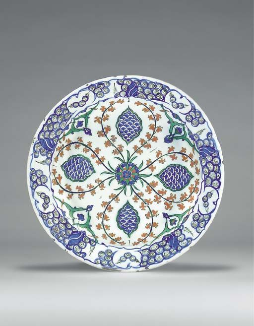 "AN IZNIK POTTERY DISH  OTTOMAN TURKEY, CIRCA 1575  With sloping rim on short foot, white interior painted in blue, green & black with red slip with a central blue & red flowerhead issuing red floral sprays forming a quatrefoil, each lobe containing a cusped ovoid cartouche with blue fish-scale, interstices with paired split-leaf panels, border with stylized wave & rock motif in blue & black, edge painted to imitate cusping, exterior with alternating paired tulip & flowerhead motifs12¼"" diam."