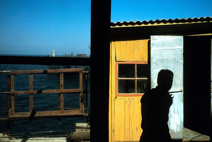 Alex Webb  AZERBAIJAN. Baku. 2001.The man made island of Neft Baslani (Oily Rocks). Worker outside hut.