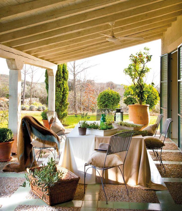 porche con comedor con sillas de hierro con plaids cojines plantas y vistas al