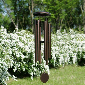 Love chimes in the garden--but it's the Bridal Wreath hedge in the background that caught my eye. This photo could have been taken in the backyard of the house where I grew up. :)