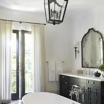 ☆Black French patio doors covered with ivory curtains hung from an oil rubbed bronze curtain rug allow natural light to stream in to a black and white Mediterranean style bathroom fitted with a freestanding oval bathtub placed in the center of the room on black and white mosaic floor tiles beneath an iron and seeded glass lantern.