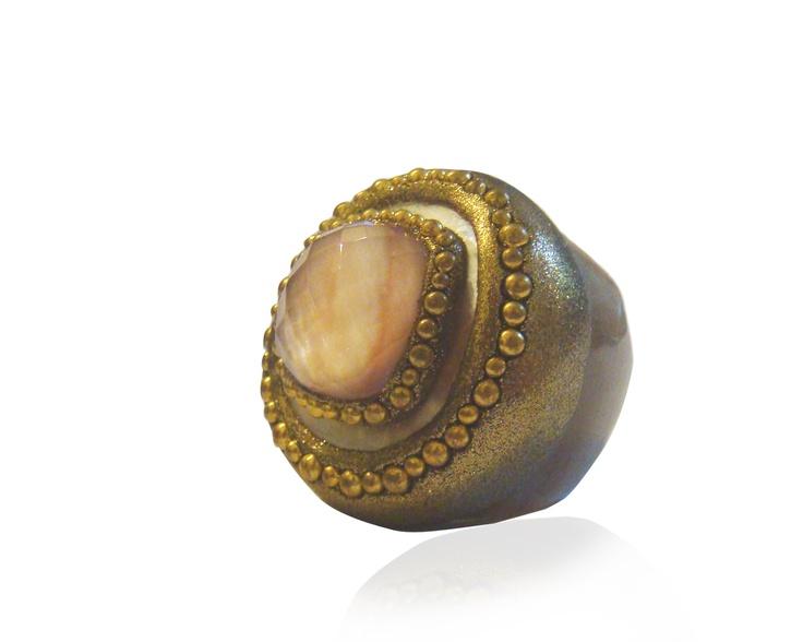 Anello gambo in corno con centrale in cristallo di rocca sfaccettato con sotto madreperla rosa, poggiato su madreperla bianca decorato con foglia di bronzo e ottone.