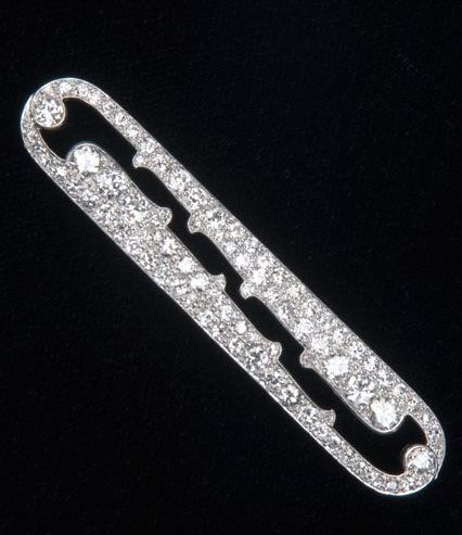 "Cartier diamond brooch in pt., ca. 1920. Pavé-set, eliptical panel, the bifurcated design formed by a curved open space. Set with fine EC and transitional-cut diamonds, approx. 4 ct. TW. 10.2 gs. GW; 2 1/2"" x 1/2""."