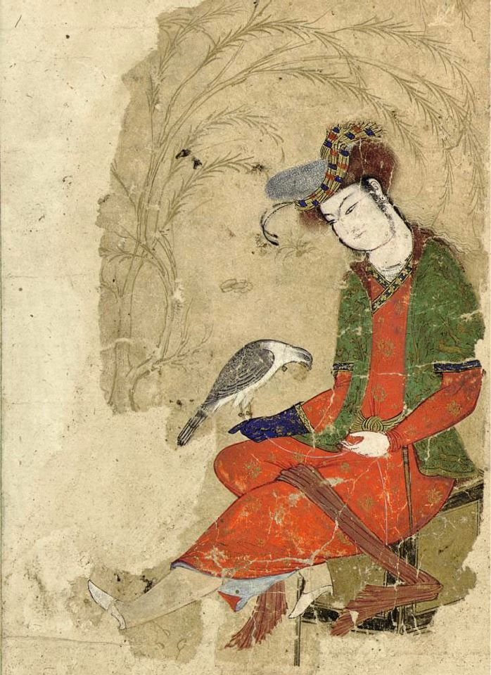 A SEATED YOUTH WITH FALCON SAFAVID IRAN, CIRCA 1600 Gouache heightened with gold on paper, a young man wearing flowing gold-heightened orange robe, green coat and elaborate turban sits upon a gold stool in a gold illuminated landscape holding a falcon on his blue-gloved hand, losses to folio 5 7/8 x 4¼in. (14.9 x 10.8cm.)