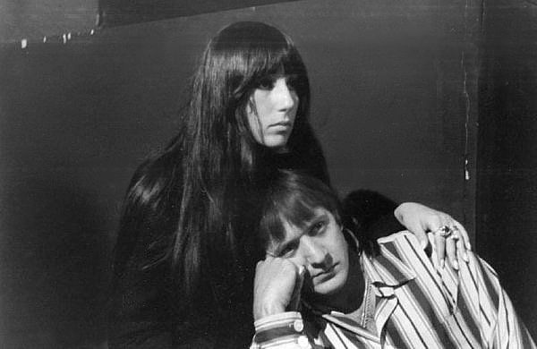 Black-and-white portrayal of a young black-haired woman and an adult man with medium length hair. They are deadpan and looking to the right. He is lying on her lap. He is supporting his face with his right hand. Her left hand is on his left shoulder.
