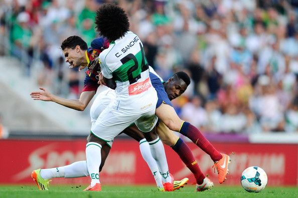Marc Bartra of FC Barcelona is brought down by Carlos Sanchez and Richmond Boakye of Elche FC during the La Liga match between Elche FC and FC Barcelona at Estadio Manuel Martinez Valero on May 11, 2014 in Elche, Spain.