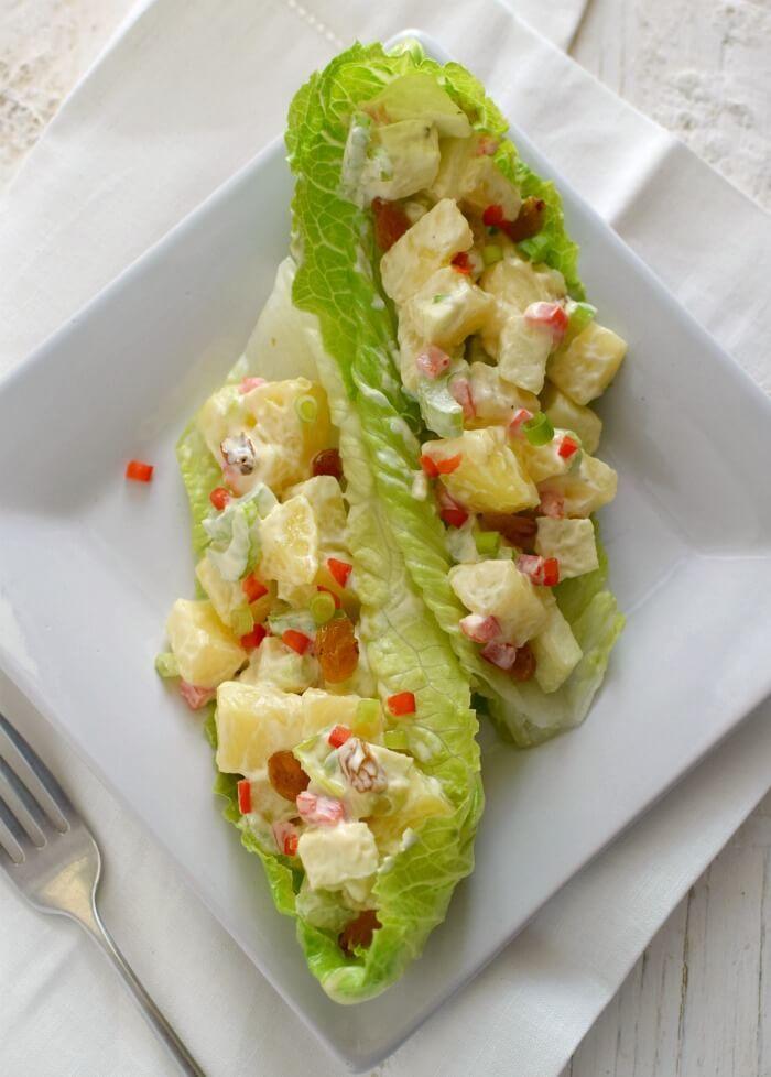 Ensalada de papas y manzana, además tiene célery, pimentón rojo, cebollines y pasas rubias, puede servirse en hojas de lechuga romana