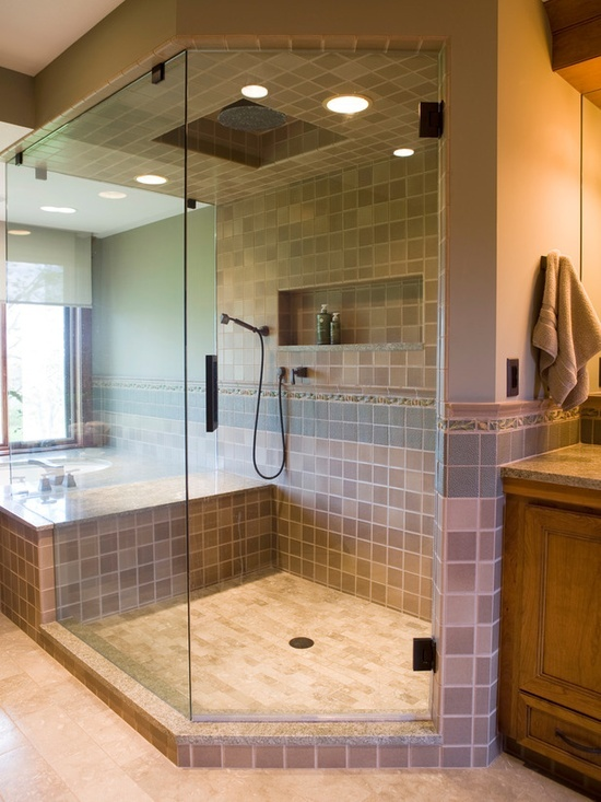 neutral toned glass shower with tile accents and recessed shelving this master bathroom features a shower with a frameless enclosure seat