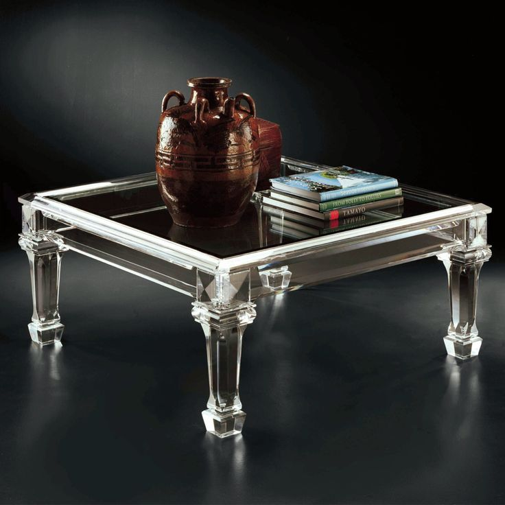 transparently glass table with luxury legs ornaments and robust glass layers above with decoration antique ceramic pot and immaculate stack of books