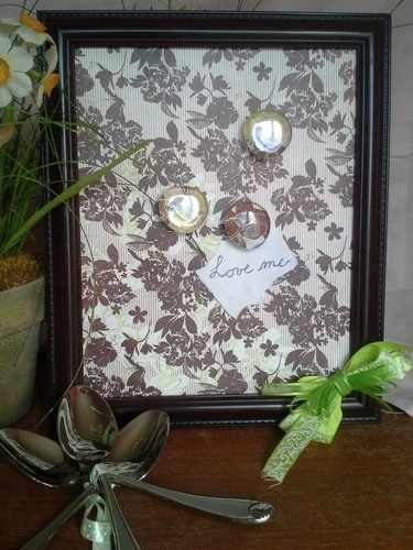 Cover a sheet of metal with scrapbook paper or fabric.  Glue inside frame.  Leave the glass off and it makes a magnetic frame.  You could also put a piece of scrapbook paper behind the glass instead of a picture and use it as a dry erase board.