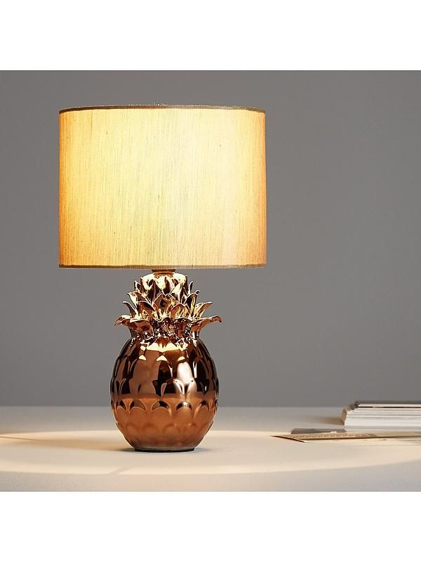 Pineapple Table Lamp – 32cm Quirky, cool and full of funky fresh charm, this totally tropical table lamp is a distinctive finishing touch for the modern home. In gold, the pineapple-shaped ceramic base has a natural shimmer that gives it a hint of glamorous style, and it's paired with a gorgeous polycotton shade to bring a unique glow to your space. Energy Rating: A++ to E depending on what bulb is used with the light.Depth: 200 MMstoneware 92% metal 2% fabric 2% PVC 2% opper 2%Height: 320…