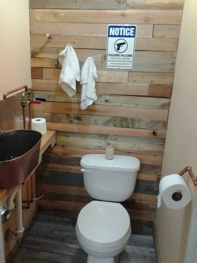 Man cave bathroom. Pallet wood floor and back wall. Copper pipes exposed and copper pipe toilet paper holder.  Shotgun shell towel hangers. And to top it off,  a home made Bacon candle