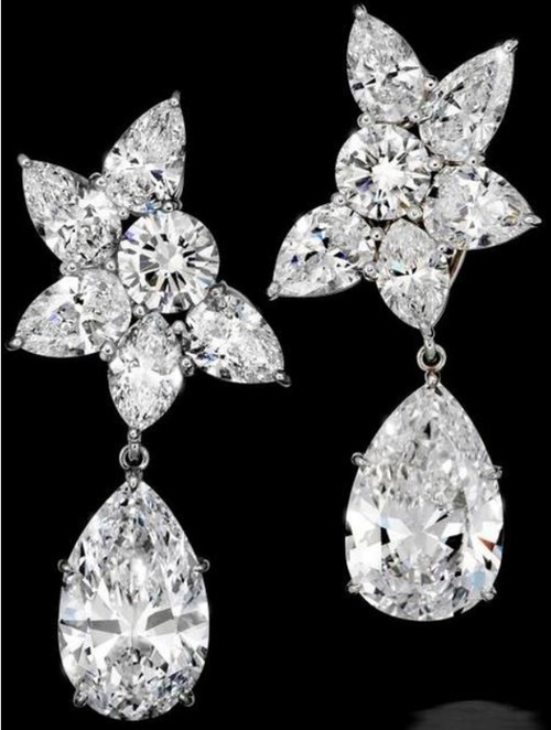 An important pair of diamond ear clips, by Harry Winston.     Each set with a detachable pear-shaped brilliant-cut diamond, weighing 6.94 and 7.00 carats, to a cluster surmount of pear, marquise and round brilliant-cut diamonds, mounted in platinum, signed 'HW', earring length 4.3cm. Via Bonhams.