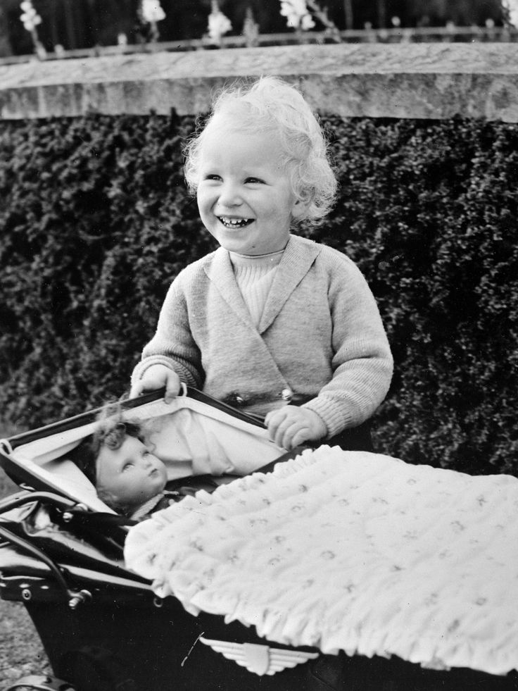 Princess Anne playing with her doll's pram in the grounds of Balmoral Castle, May 1953,