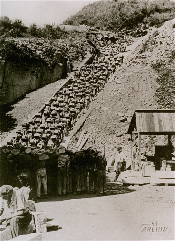 """Prisoners carry large stones up the """"stairs of death"""" (Todesstiege) from the Wiener Graben quarry at the Mauthausen concentration camp."""
