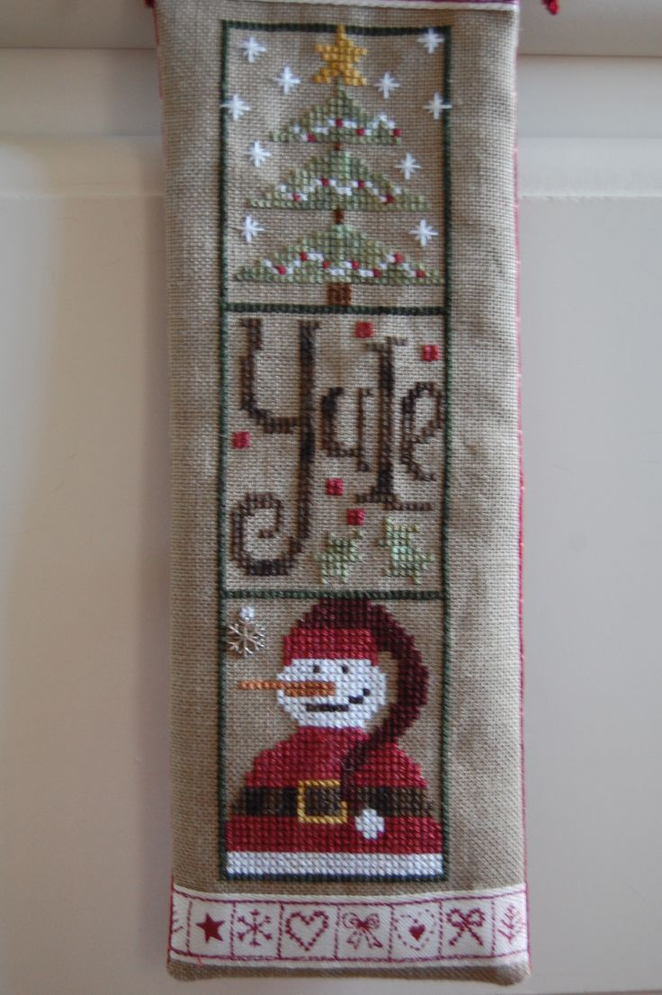 embroidery by Jackie for a Christmas hanger decoration, 8 cm x 24 cm, backed with a star patterned uneven dyed cotton, and a lustrous burgundy cord on a cinnamon stick