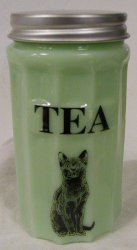 Jade Glass Jadite Canister TEA Sitting Cat Design * Caz Metal Tops. Sharp lined sides.  The flat frontace that holds the canisters ingredient label.  This is cast in a green milk glass. Also known as Jade or Jadiete.  Each piece has the  decals hand fired in Western Pennsylvania.   The measurements of seven and a half inches by four inches are set by the depression glassware that would fit into classic cabinets.