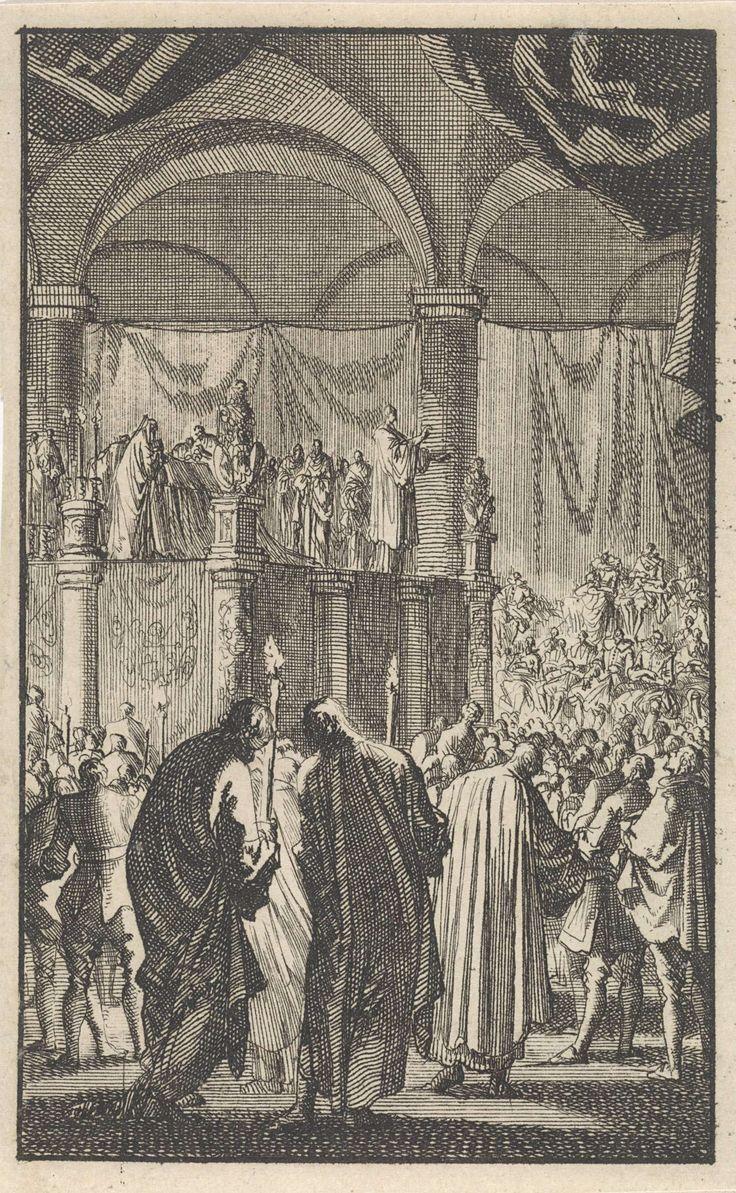 Jan Luyken | Lijkstatie van Filips II, 1598, Jan Luyken, 1699 | Een interieur van een kerk met de lijkstatie van de Spaanse koning Filips II. Op een verhoging in een kerk ligt de kist. Een man houdt een toespraak voor de menigte. Op de voorgrond twee mannen met kaarsen.