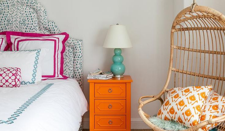 Blue and orange girl's bedroom features a curved headboard upholstered in Brunschwig & Fils Les Touches Fabric on bed dressed in pink and blue bedding placed next to an orange nightstand and a teal triple gourd lamp as well as a Two's Company Hanging Rattan Chair lined with orange pillows.