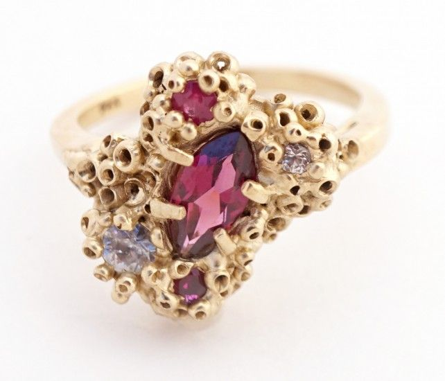 """The """"Safta"""" 14-karat yellow gold ring from Ruta Reifen is set with white sapphires, rubies and a marquise-shaped faceted rhodolite ($1,680)."""