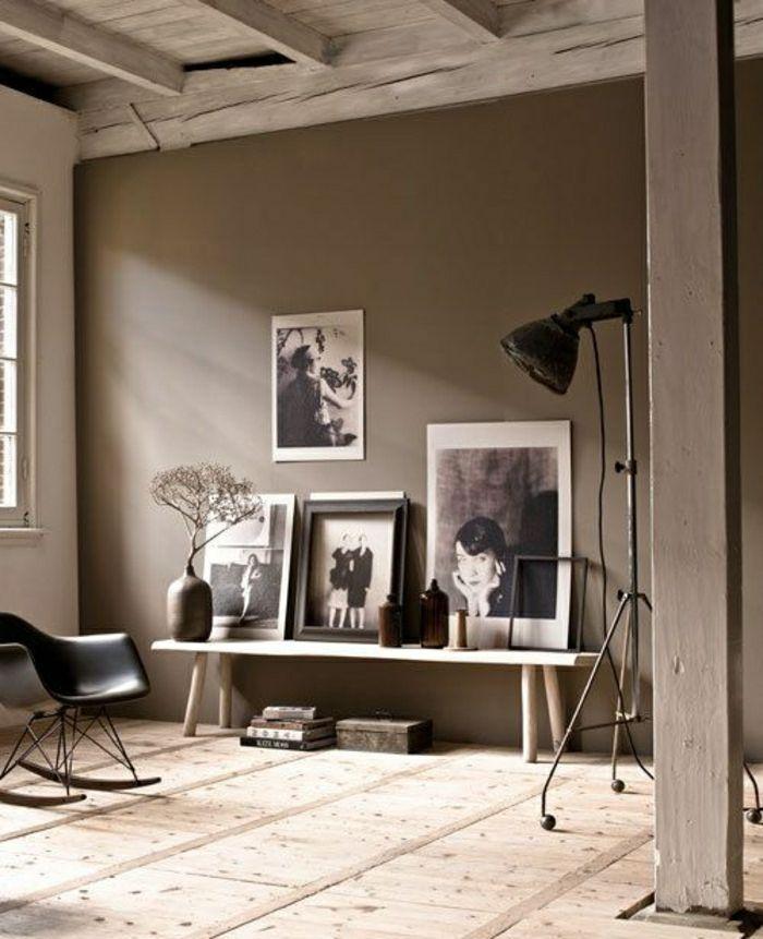 un salon vaste sol en bois, chaise berçante noire, mur taupe, plafond en bois