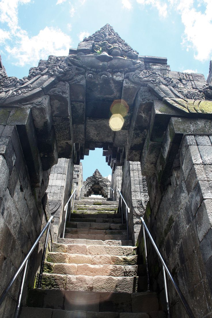 Lens flare at the Borobudur stairs and Kala arches entrance. Borobudur is the 8th century Buddhist monument took shape as a giant Mandala-mountain. The stairs took pilgrim from Kamadhatu (realm of desire}, through Rupadhatu (realm of forms and shapes), and finaly elevated to a higher spiritual plane of Arupadhatu (realm of formlesness). Central Java, Indonesia.