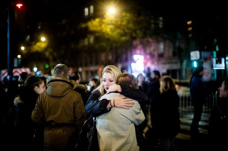 Friends hug after the attacks at Le Bataclan concert hall.  Paris attacks.