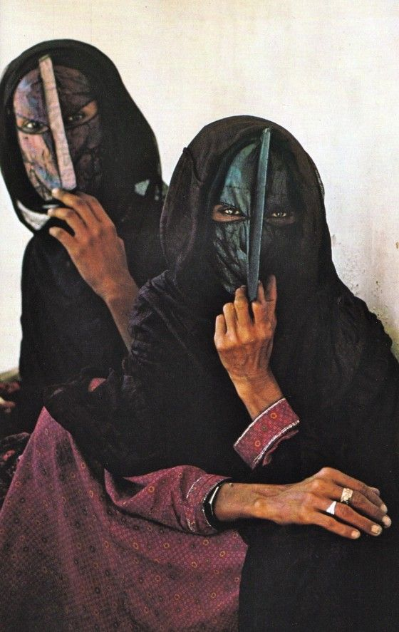 'Startled by strangers, two Bedouin women of the central desert region clutch full-face masks, rarely seen elsewhere in Oman, as they wait for a doctor to arrive by plain at the samll dispensary in Sharbatat'. From 'Oman: Guardian of the Gulf', author and photographer Thomas and Lynne Abercrombie, page 375, National Geographic, September 1981