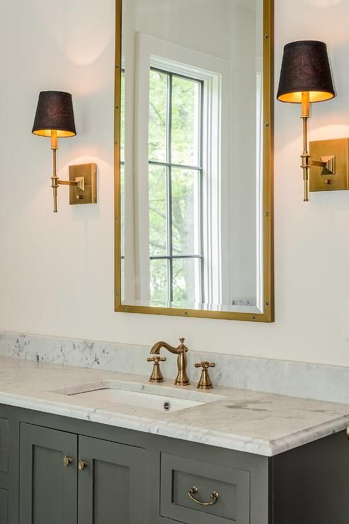 Mediterranean bathroom features a gray vanity adorned with brass hardware topped with carrera marble fitted with a rectangular sink and an antique brass faucet under a brass rivet mirrors, Restoration Hardware Rivet Medicine Cabinet, illuminated by brass sconces with black shades.